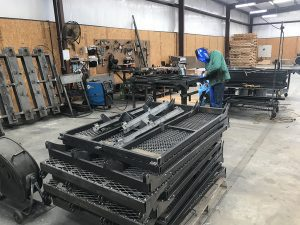 A welder works at Super Lawn Trucks.