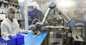Employee in a manufacturing plant works alongside a collaborative robot.