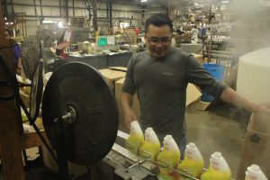 Man works on a production line making cleaning products.