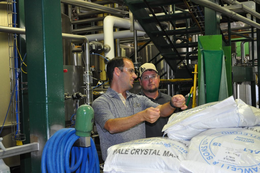Damon Nix, senior project manager at the Georgia Manufacturing Extension Partnership, discusses ergonomic solutions for lifting bags of malt with Bobby Epperson, operations training and safety manager at Terrapin Brewery in Athens, Georgia.