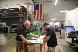E. Don Smith discusses orders with a Precision Products Inc. employee.