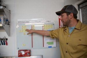 King of Pops manager points to visual management board.