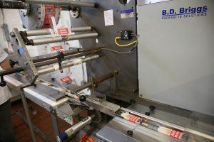 Popsicles go through a packaging machine to prepare for shipping or distribution.