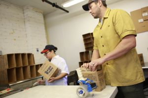 King of Pops employees pack popsicles into boxes to prepare for shipping.