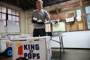 King of Pops employee packs popsicles into cart.