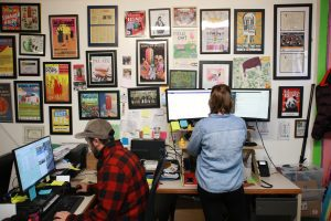 King of Pops employees work in their administrative office, decorated with awards and framed magazine stories about the company.