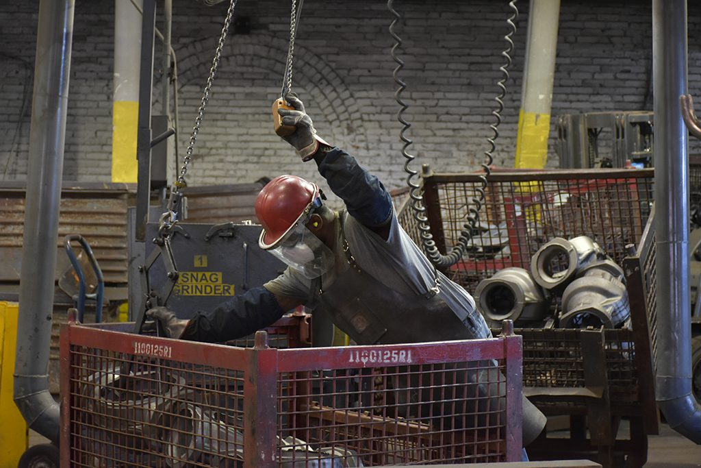 Employee at Goldens's Foundry and Machine Co. working in the grinding area to finish parts made at the foundry.