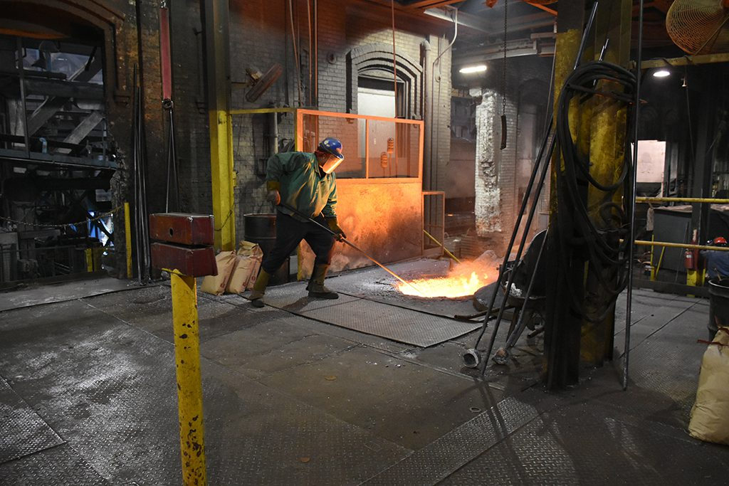 Employee at Goldens' Foundry prepares molten metal to be poured into molds.