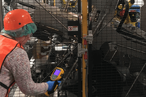 Paula Glover, Enterprise Engineer with Shaw Industries, uses a thermal camera to check for hot spots on a robotic arm.